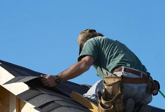 Roofing contractor installs composite tiles